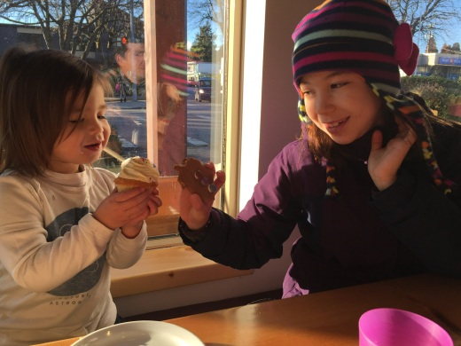 """Charlie and Addison doing a """"cheers"""" with their cookie and cupcake."""