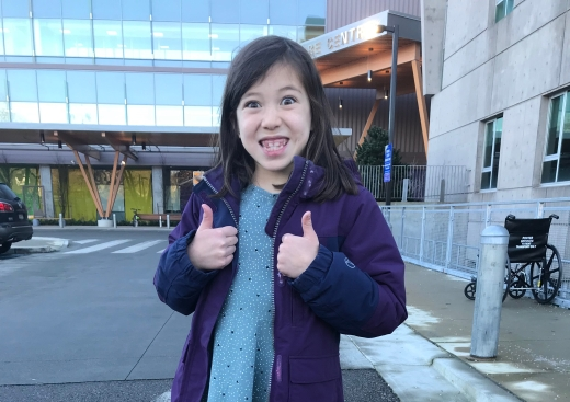 Addison standing outside BCCH giving thumbs up.